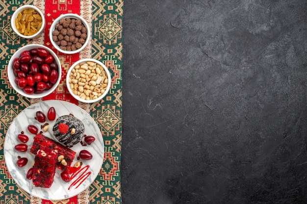 Draufsicht rote hartriegel mit nüssen nougat und rosinen auf grauem hintergrund süßigkeiten zucker frucht süße nuss