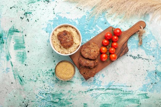 Draufsicht rote kirschtomaten mit fleischkoteletts auf blauer oberfläche