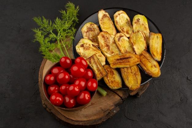 Draufsicht rote kirschtomaten zusammen mit gemüse und gekochten auberginen auf dem braunen schreibtisch und dem dunklen boden