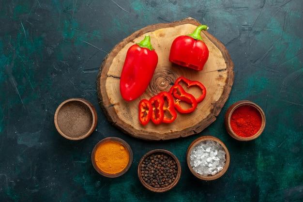 Draufsicht rote paprika mit verschiedenen gewürzen auf dunkelgrüner oberfläche gemüse scharf scharfes essen