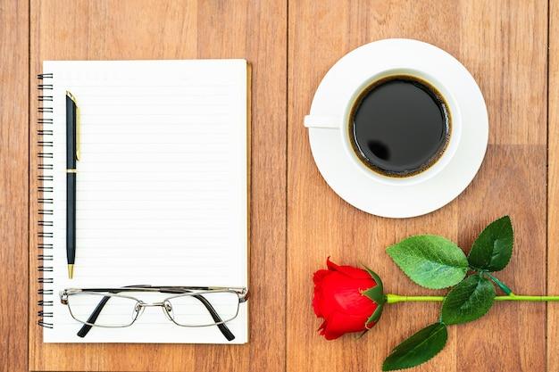 Draufsicht rote rosen und kaffeetasse auf holztisch und stift auf notizblock auf holzdeck