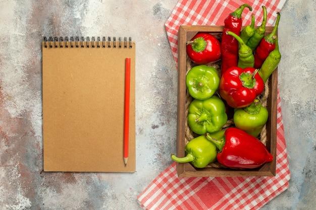 Draufsicht rote und grüne paprikaschoten peperoni in der holzkiste auf kariertem tischtuch-notizbuch-rotstift auf nackter oberfläche