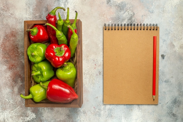 Draufsicht rote und grüne paprikaschoten peperoni in holzkasten-notizbuchrotstift auf nackter oberfläche