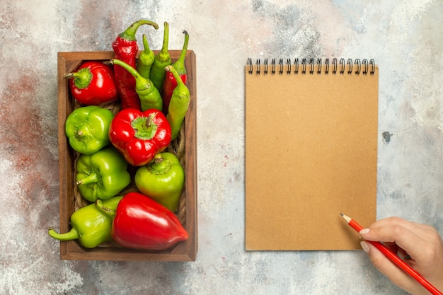 Draufsicht rote und grüne paprikaschoten peperoni in holzkasten-notizbuchrotstift in weiblicher hand auf nackter oberfläche