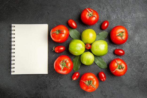 Draufsicht rote und grüne tomaten lorbeerblätter um eine kirschtomate und ein notizbuch auf dunklem grund