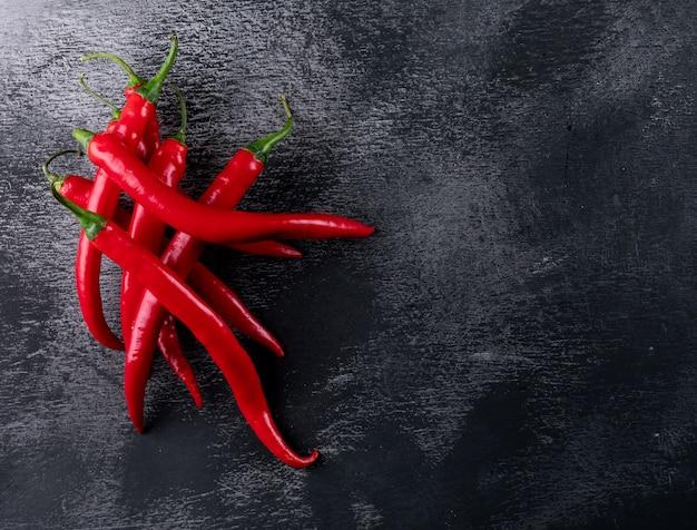 Draufsicht roter chili-pfeffer mit kopierraum rechts auf schwarzem stein horizontal