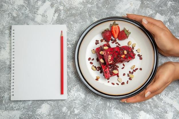Draufsicht roter nougat in scheiben geschnitten mit nüssen und frischen roten erdbeeren auf weißer oberfläche