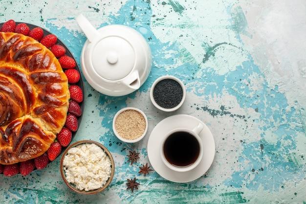 Draufsicht runde köstliche torte mit frischen erdbeeren auf hellblauem schreibtisch