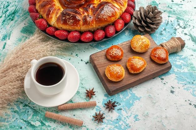Draufsicht runde köstliche torte mit kleinen erdbeerkuchen und tasse tee auf hellblauer oberfläche