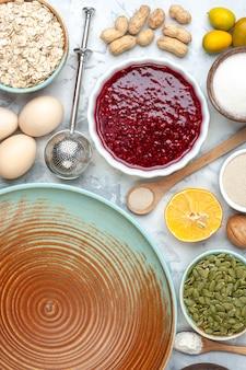 Draufsicht runde tellerschalen mit marmelade kürbiskerne mehl hafer eier erdnüsse holzlöffel