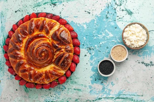 Draufsicht runder köstlicher kuchen gebackener und süßer kuchen mit erdbeeren auf blauer oberfläche