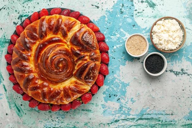 Draufsicht runder köstlicher kuchen mit frischen erdbeeren auf der blauen oberfläche