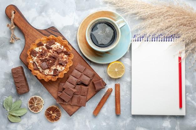 Draufsicht sahne kleiner kuchen mit schokoriegel notizblock und tee auf dem hellen schreibtisch süße kuchen zuckercreme schokolade