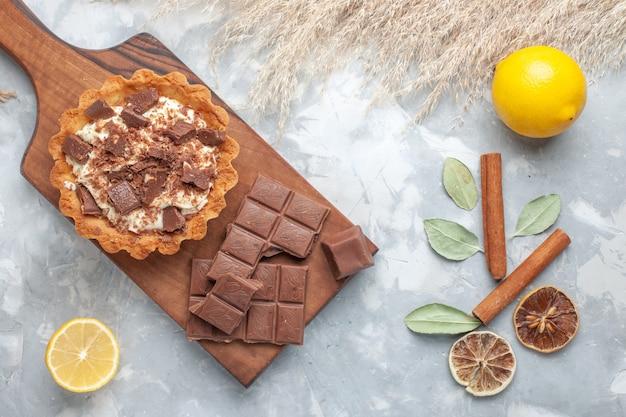 Draufsicht sahne kleiner kuchen mit schokoriegeln zitronen auf dem hellen schreibtisch süßer kuchen zuckercreme schokolade