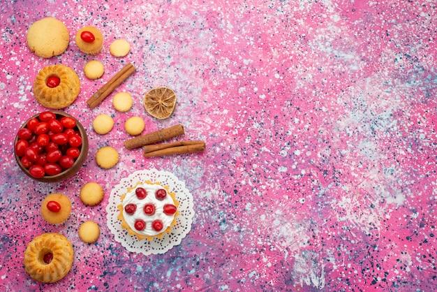Draufsicht-sahnetorte mit frischen roten preiselbeeren zusammen mit zimtplätzchen auf dem lila schreibtischkekszuckersüß