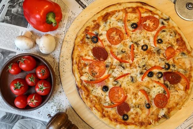 Draufsicht salami-pizza auf einem tablett mit pilzen und tomaten mit bulgarischem rotem pfeffer