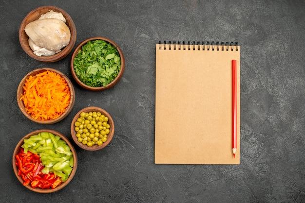 Draufsicht salatzutaten mit huhn und grün auf dunklem tischgesundheitssalat