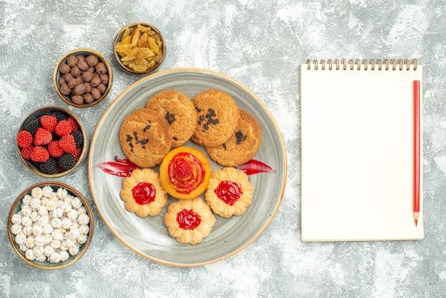 Draufsicht sandplätzchen mit süßen keksen und bonbons auf einem weiß