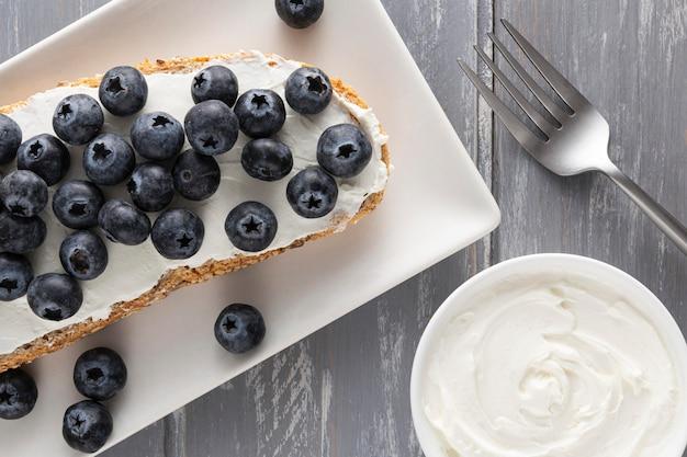 Draufsicht-sandwich mit frischkäse und blaubeeren auf teller