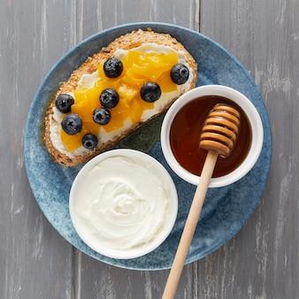 Draufsicht-sandwich mit frischkäse und früchten auf teller mit honig