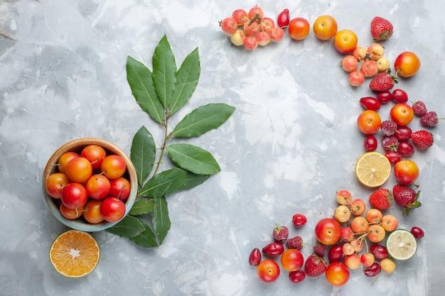 Draufsicht sauerkirschpflaumen mit zitrone und anderen früchten auf dem hellen schreibtisch