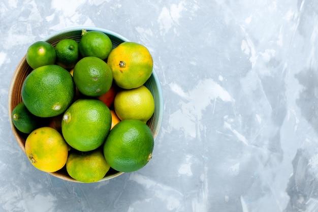 Draufsicht saure frische mandarinen mit zitronen auf dem hellweißen schreibtisch
