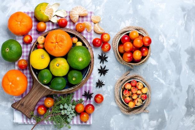 Draufsicht saure frische mandarinen mit zitronen und pflaumen auf dem hellweißen schreibtisch