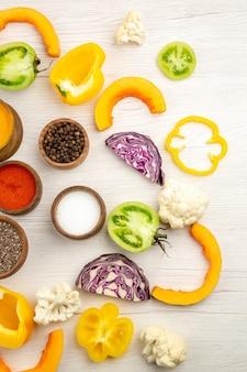 Draufsicht schalen mit gewürzen geschnitten paprika blumenkohl geschnitten rotkohl geschnitten grüne tomaten auf weißem grund