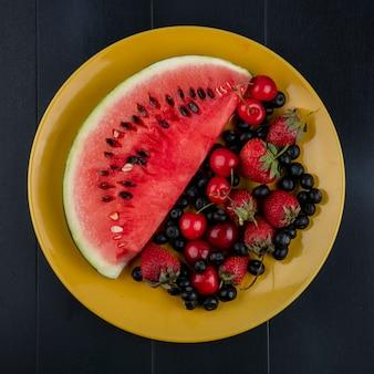 Draufsicht scheibe der wassermelone mit kirschen blaubeeren und erdbeeren auf einem gelben teller auf einem schwarzen hintergrund