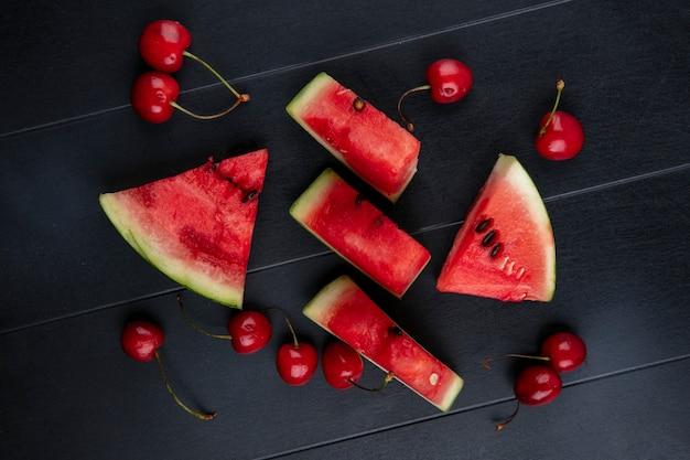Draufsicht scheiben der wassermelone mit kirschen auf einem schwarzen hintergrund