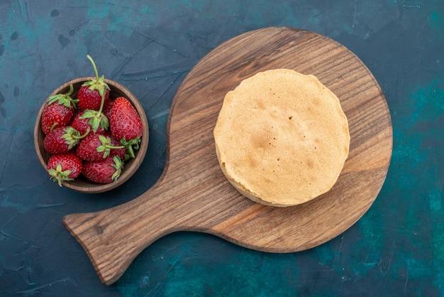 Draufsicht schlichter backteig rund gebacken mit erdbeeren auf dem dunkelblauen schreibtisch