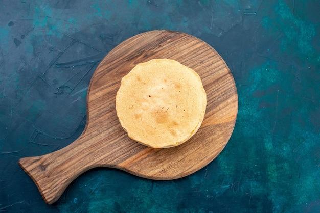 Draufsicht schlichter kuchenteig, rund gebacken auf der dunkelblauen oberfläche