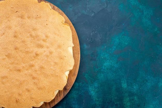 Draufsicht schlichter kuchenteig rund gebacken auf dunkelblauem schreibtisch