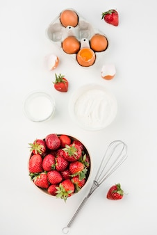 Draufsicht schneebesen mit erdbeeren und eiern