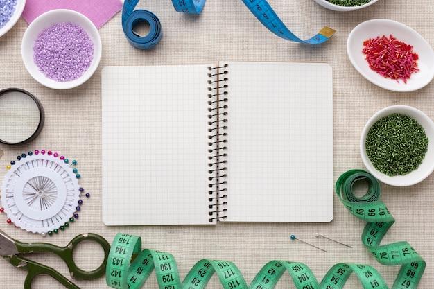 Draufsicht schneiderwerkzeuge und elementsortiment mit leerem notizbuch