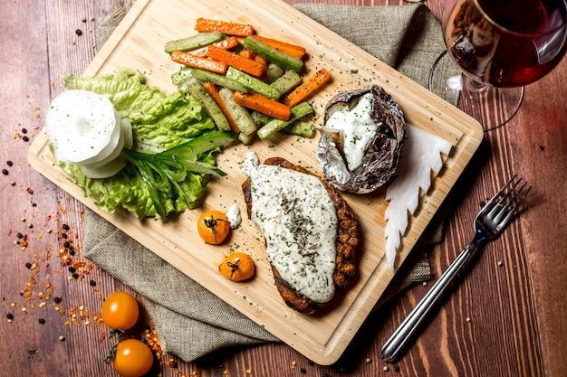 Draufsicht schnitzel mit frischkäse mit ofenkartoffeln in folie und mit gemüse auf einem brett