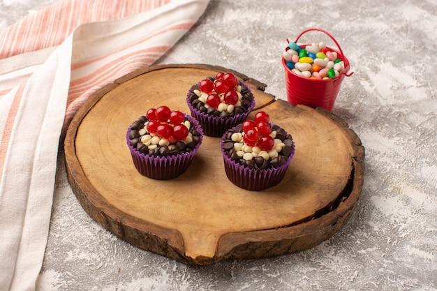 Draufsicht schokoladen-brownies mit preiselbeeren und bonbons überall auf dem hellen schreibtischkuchenkeks süßer backteig