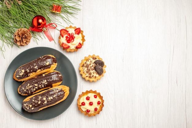 Draufsicht schokoladen-eclairs auf den grauen tellertörtchen und den kiefernblättern mit weihnachtsspielzeug auf der linken seite des weißen holzbodens