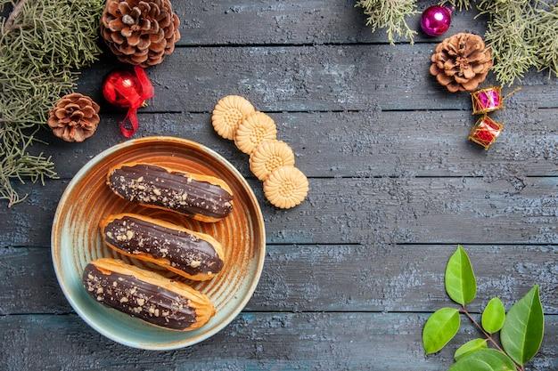 Draufsicht schokoladen-eclairs auf einem ovalen teller tannenzapfen weihnachtsspielzeug tannenbaum verlässt kekse und blätter auf dunklem holzboden mit kopierraum