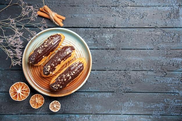 Draufsicht schokoladen-eclairs auf ovalem teller getrockneten blumenzweig und getrockneten zitronen auf der linken seite des dunklen holztischs mit kopierraum