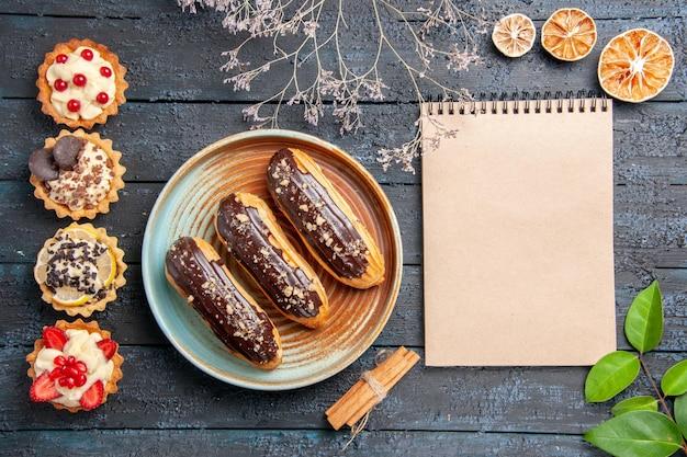Draufsicht schokoladen-eclairs auf ovalem teller getrockneter blumenzweig zimtgetrocknete orangen hinterlässt ein notizbuch und vertikale reihenkuchen auf dem dunklen holztisch