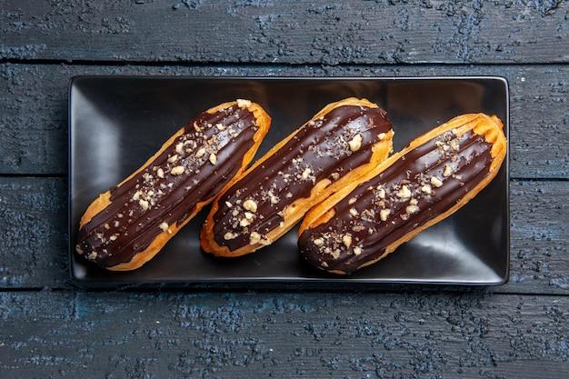 Draufsicht schokoladen-eclairs auf rechteckplatte auf dunkler holzoberfläche