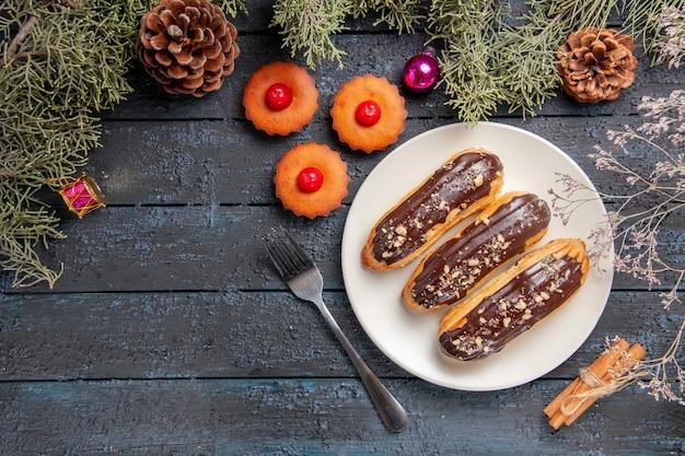Draufsicht schokoladen-eclairs auf weißen ovalen platten-tannenbaumzweigen und zapfenweihnachtsspielzeugen ein gabelzimt auf dunklem holztisch mit kopienraum