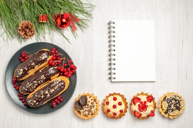 Draufsicht schokoladen-eclairs und johannisbeeren auf dem grauen teller ein notizbuch törtchen am boden und kiefernblätter mit weihnachtsspielzeug auf dem weißen holzboden