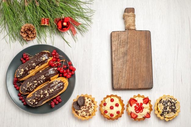 Draufsicht schokoladen-eclairs und johannisbeeren auf dem grauen teller ein schneidebrett törtchen und kiefernblätter mit weihnachtsspielzeug auf dem weißen holzboden