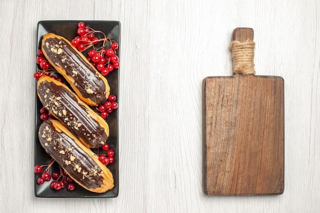 Draufsicht schokoladen-eclairs und johannisbeeren auf dem schwarzen rechteckigen teller auf der linken seite und einem schneidebrett auf der rechten seite des weißen holzbodens