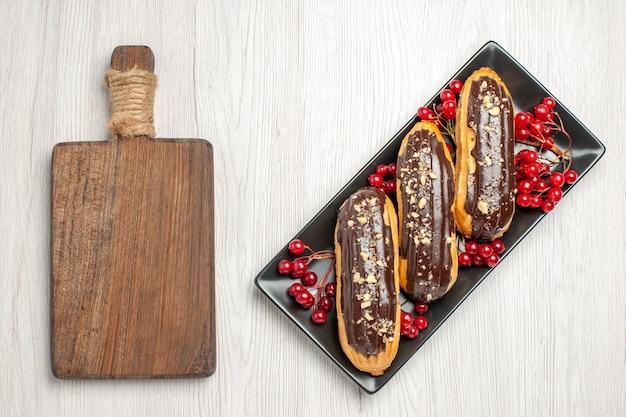 Draufsicht schokoladen-eclairs und johannisbeeren auf dem schwarzen rechteckigen teller auf der rechten seite und einem schneidebrett auf der linken seite des weißen holzbodens