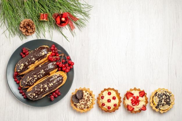 Draufsicht schokoladen-eclairs und johannisbeeren auf den grauen plattentörtchen unten und kiefernblätter mit weihnachtsspielzeug auf dem weißen holzgrund
