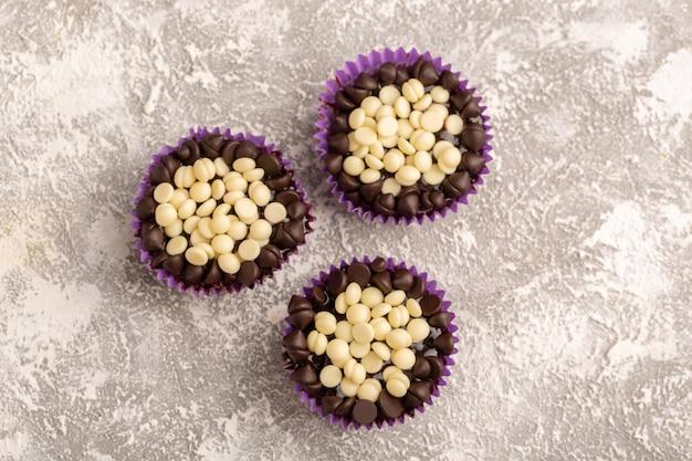 Draufsicht schokoladenchips weiß und dunkel in lila papieren auf dem hellen hintergrund schokoladenkuchen zucker süß backen