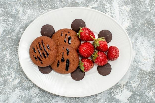 Draufsicht schokoladenkekse erdbeeren und runde pralinen auf dem weißen ovalen teller auf dem grauweißen grund